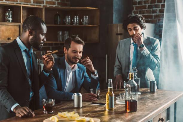 knappe jonge multi-etnisch mannen in pakken sigaren te houden terwijl het feesten samen - guy with cigar stockfoto's en -beelden