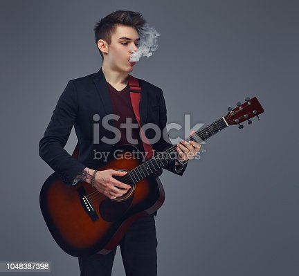istock Handsome young musician with stylish hair in elegant clothes exhales smoke while playing acoustic guitar. 1048387398