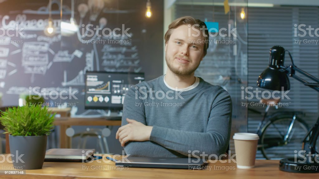 Handsome Young Office Employee Finishes His Work Closes Laptop Computer and Charmingly Smiles on Camera. He's Working in the Creative Stylish Office. stock photo