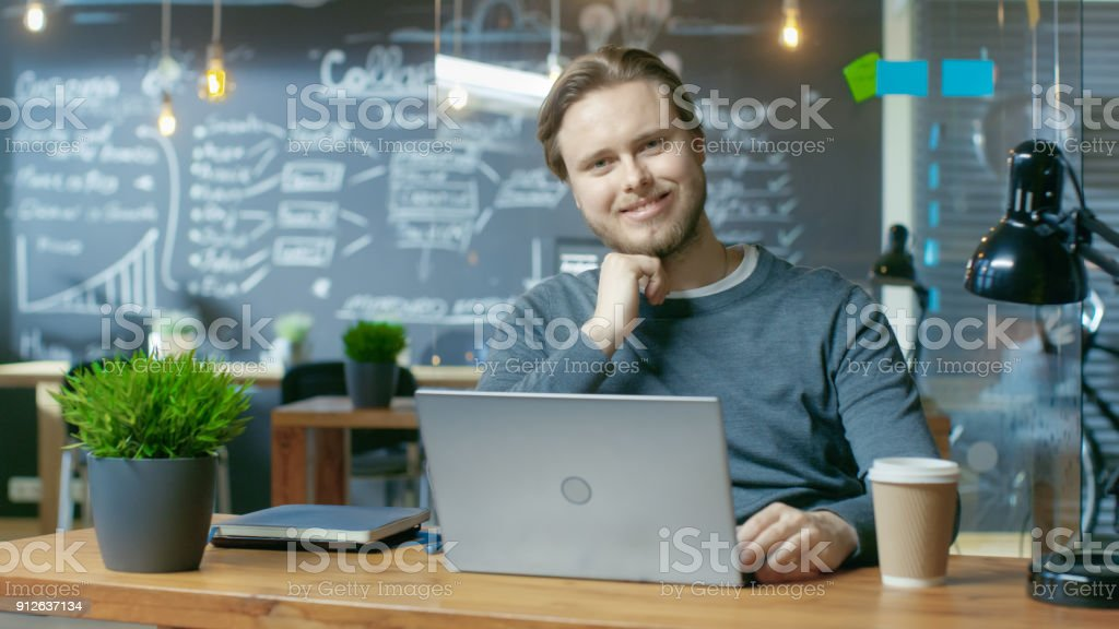Handsome Young Office Employee Thinks on a Problem Solution While Typing on a Laptop Computer,  He Charmingly Smiles on Camera. He's Working in the Creative Stylish Office. stock photo