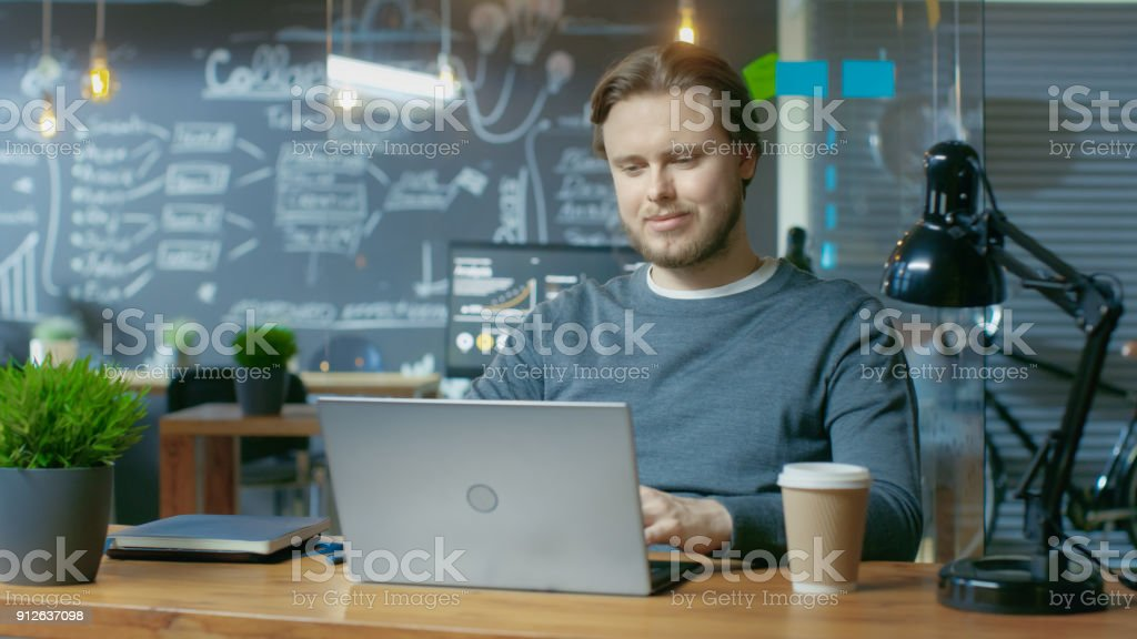 Handsome Young Office Employee Typing on a Laptop Computer,  He Charmingly Smiles. He's Working in the Creative Stylish Office. stock photo