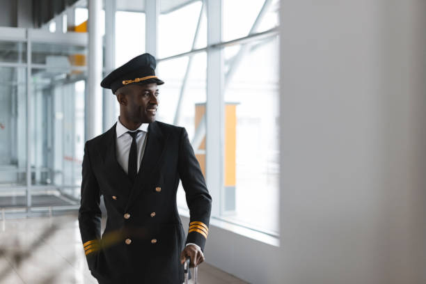 handsome young pilot with luggage at airport looking away stock photo