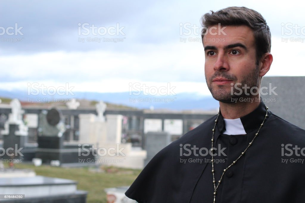 Handsome young priest close up looking away stock photo