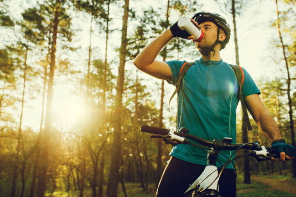 Handsome young professional cyclist dressed in cycling clothing and protective helmet feeling free and happy, drinking water from the bottle, enjoying bicycle in warm spring. Recreation of sportsman. stock photo
