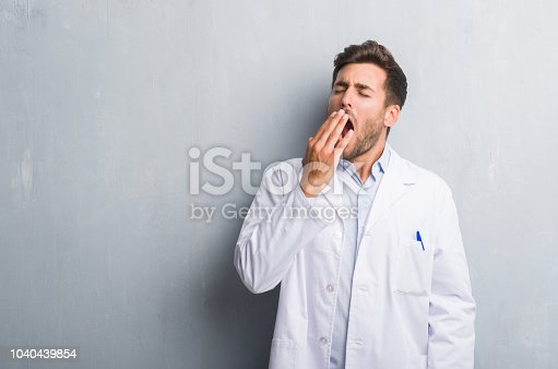 istock Handsome young professional man over grey grunge wall wearing white coat bored yawning tired covering mouth with hand. Restless and sleepiness. 1040439854