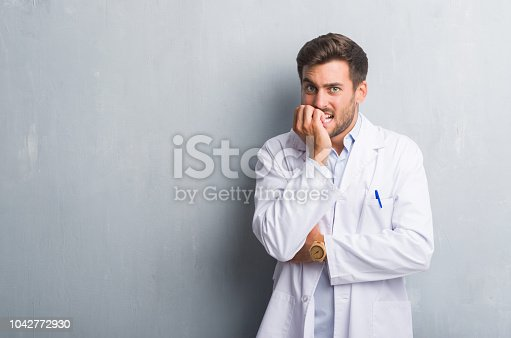 istock Handsome young professional man over grey grunge wall wearing white coat looking stressed and nervous with hands on mouth biting nails. Anxiety problem. 1042772930