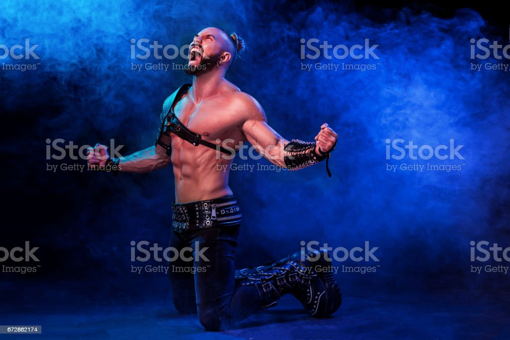 Handsome young sexy man with beautiful muscular chest in interesting costume on the scene stock photo