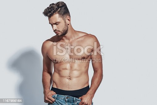 Handsome young shirtless man taking off his jeans while standing against grey background