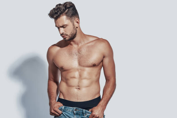 Handsome young shirtless man taking off his jeans while standing against grey background Handsome young shirtless man taking off his jeans while standing against grey background shirtless male models stock pictures, royalty-free photos & images