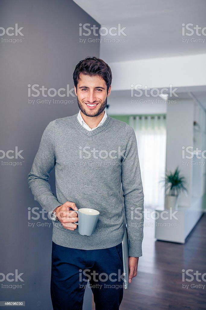 Handsome young smiling businessman working from home stock photo