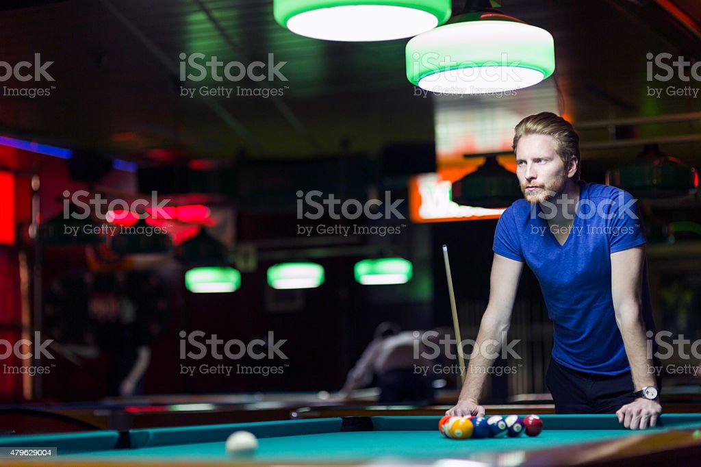 Handsome young snooker player bending over the table stock photo