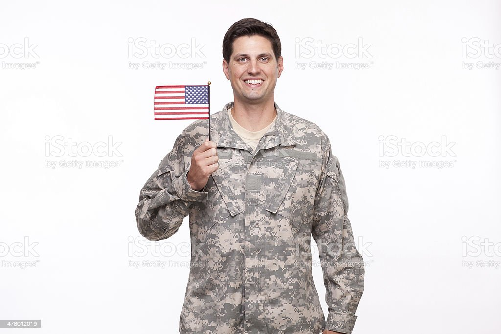 handsome young soldier posing with an American flag royalty-free stock photo