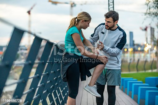 istock Handsome Young Sports Woman Have Physical Injury of Knee During a Practice with his Friend 1199486728