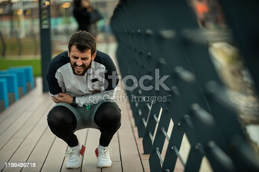 istock Handsome Young Sportsman Have Injury of Stomach During a Practice 1199486718