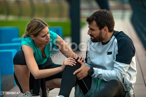An Athlete has Pain in his Knee During a Relaxation Exercise near the River Bank with his Female Teammate. Handsome Young Sportsman in Sports Suit is Having a Knee Injury During Morning Running in the City and his Girlfriend is Giving her Assistance to Solve the Problems.