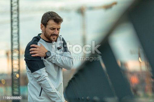 Sportsman has Pain in his Shoulder During a Relaxation Exercise near the River Bank. Handsome Young Athlete in Sports Suit is Having a Shoulder Injury During Morning Running in the City.