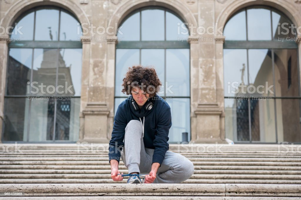 Handsome young sportsman in tracksuit tying up shoelaces royalty-free stock photo