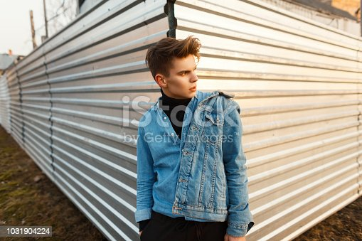 846124694istockphoto Handsome young stylish man in trendy denim clothes posing near a metal wall on a spring day 1031904224
