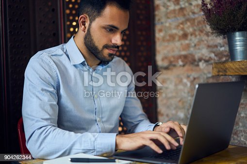 904263506 istock photo Handsome young successful owner of floral shop typing on laptop computer text of business contract searching information on internet sitting in modern interior cafe using laptop computer and free wifi 904262344