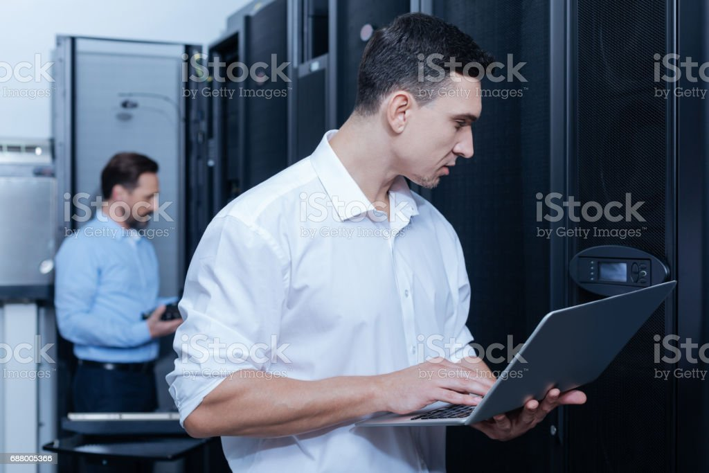 Handsome young technician looking at the control panel royalty-free stock photo