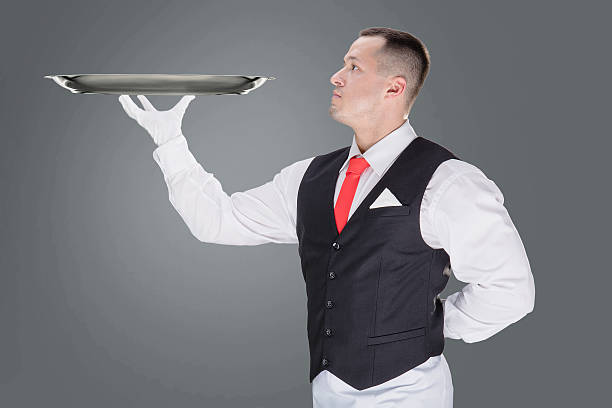 Handsome young waiter in gloves and red cravat – Foto