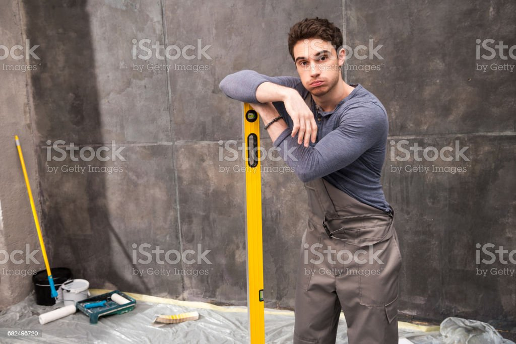 Handsome young worker leaning on level tool and looking at camera, renovation concept royalty-free stock photo