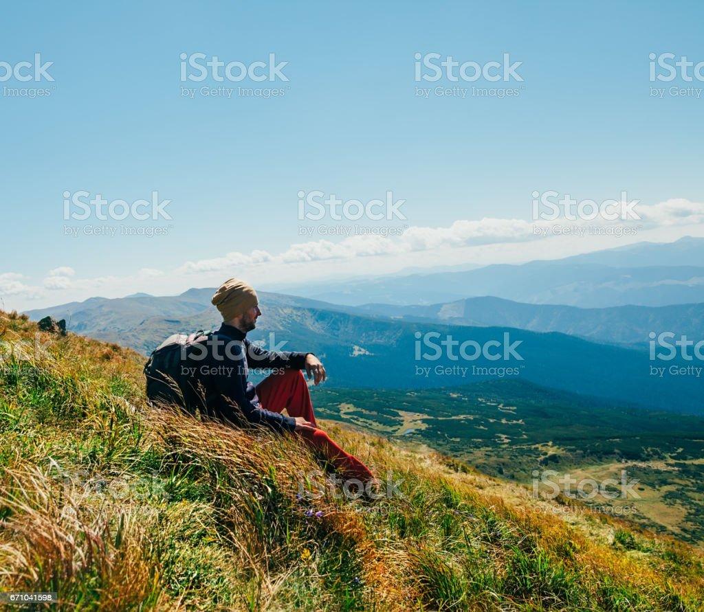 Handsomeyoung homem sentado na falésia rochosa e curtindo a natureza - foto de acervo