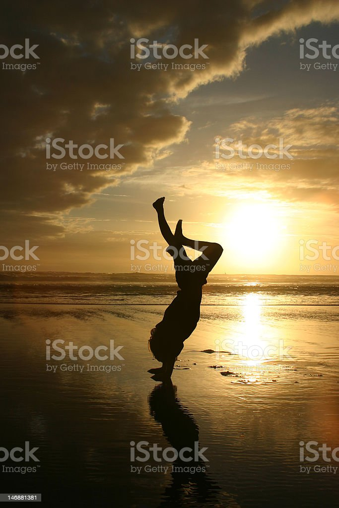 Handstand silhouette on beach stock photo