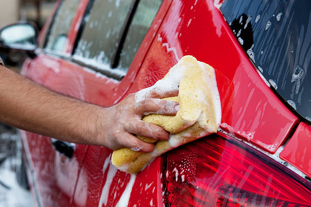 handwashing a red car with soap and sponge - handwashing stock photos and pictures