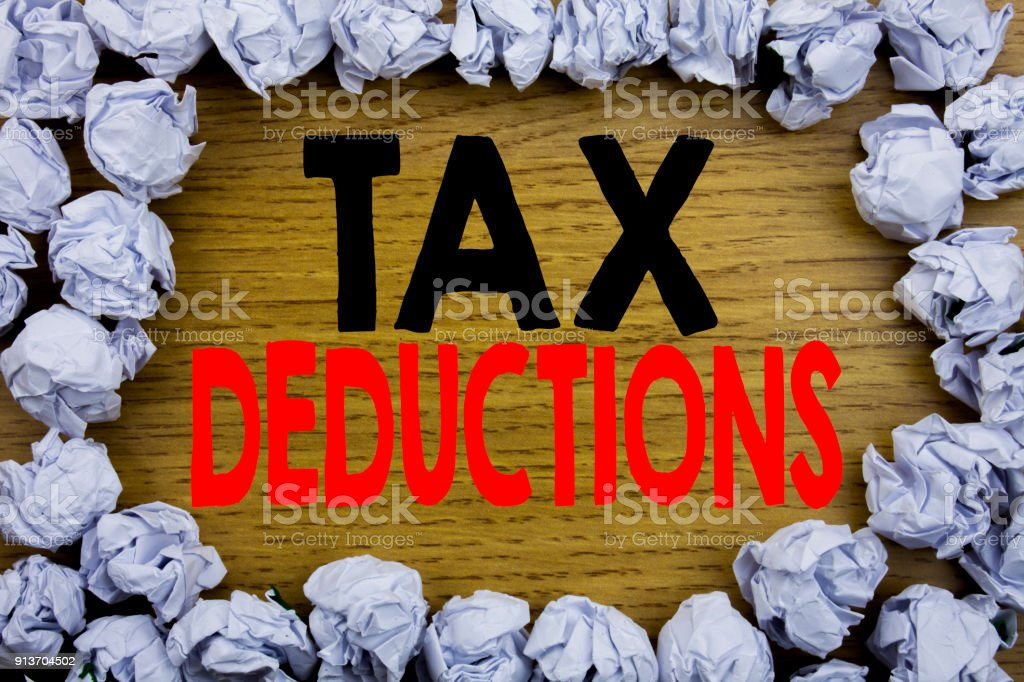 Handwriting Announcement text showing Tax Deductions. Business concept for Finance Incoming Tax Money Deduction written on wooden wood background with space on old background with folded paper balls stock photo