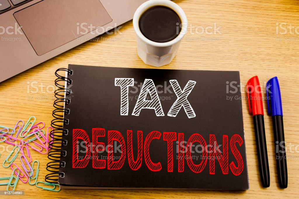 Handwriting Announcement text showing Tax Deductions. Business concept for Finance Incoming Tax Money Deduction written on notebook book on the wooden background in the Office with laptop coffee stock photo