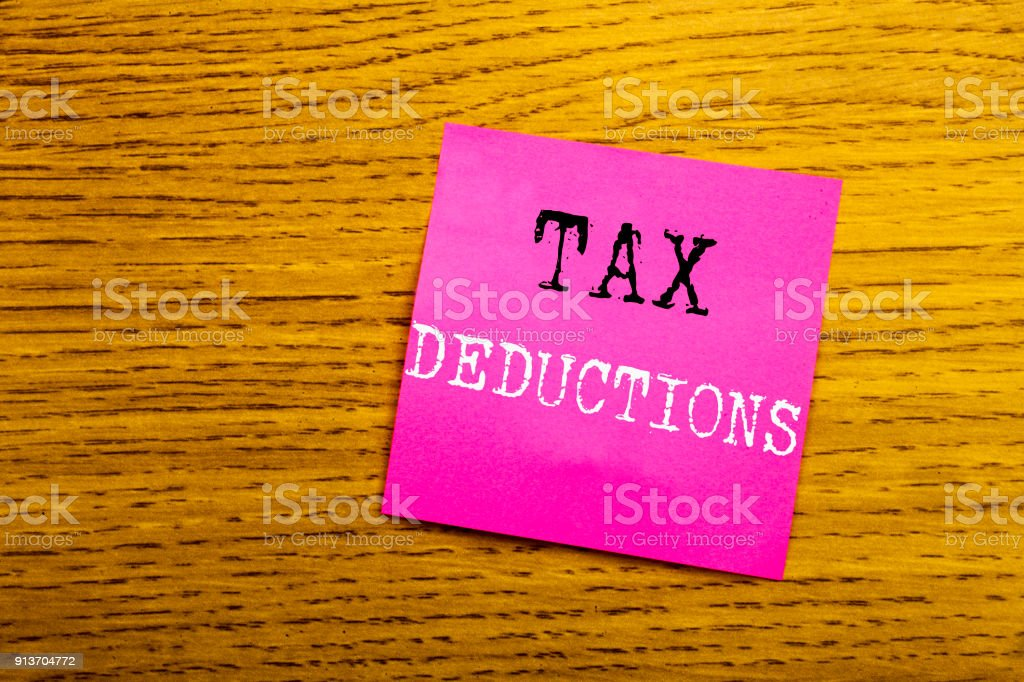 Handwriting Announcement text showing Tax Deductions. Business concept for Finance Incoming Tax Money Deduction written on sticky note empty paper, wooden background with copy space, sunglasses. stock photo