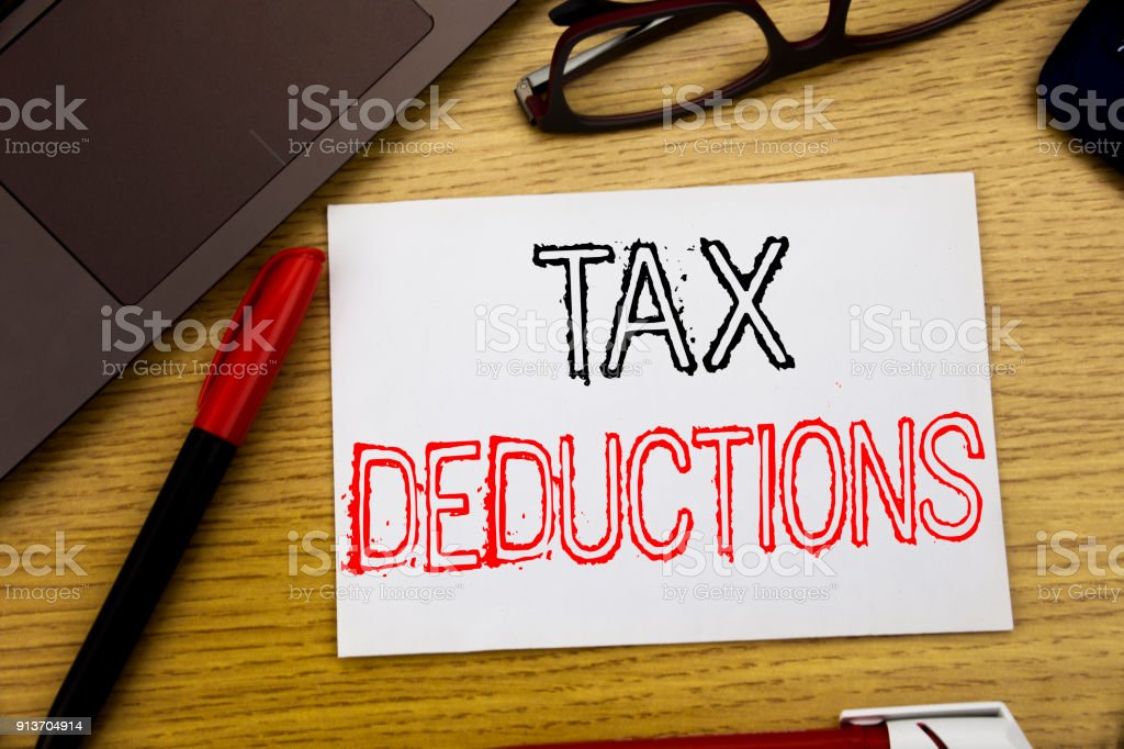 Handwriting Announcement text showing Tax Deductions. Business concept for Finance Incoming Tax Money Deduction written on paper, wooden background in office with copy space, marker pen and glasses stock photo