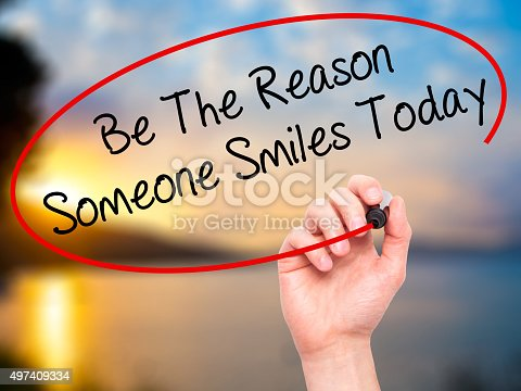 Man Hand writing Be The Reason Someone Smiles Today with black marker on visual screen. Isolated on nature. Business, technology, internet concept.
