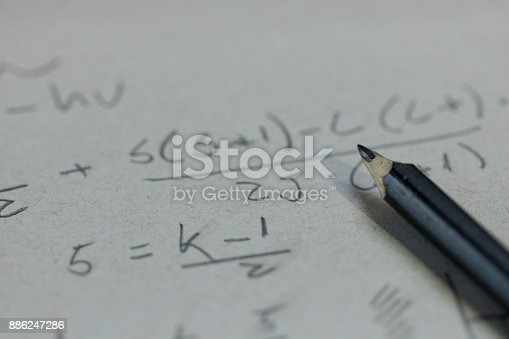 1148553584istockphoto Handwriting formula on a paper with pen 886247286