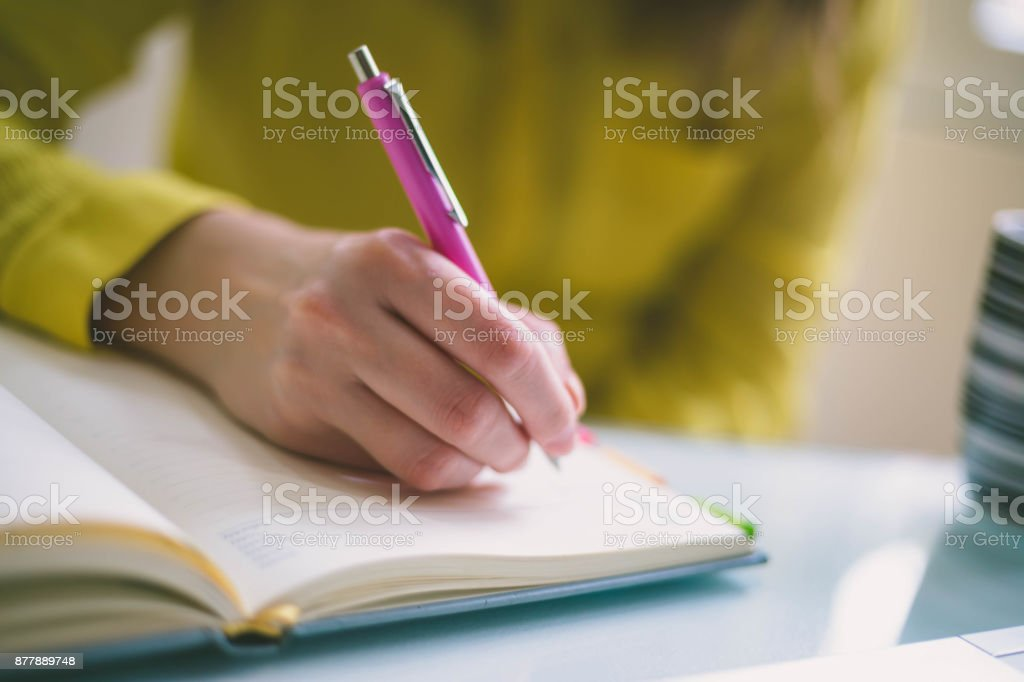 Handwriting, hand writes with a pen in a notebook stock photo