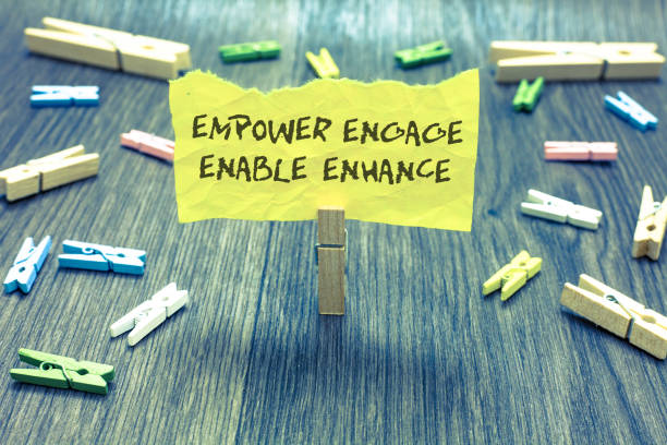 handwriting text empower engage enable enhance. concept meaning empowerment leadership motivation engagement paperclip hold written torn page many clips laid on bluish wooden floor. - employee engagement stock photos and pictures