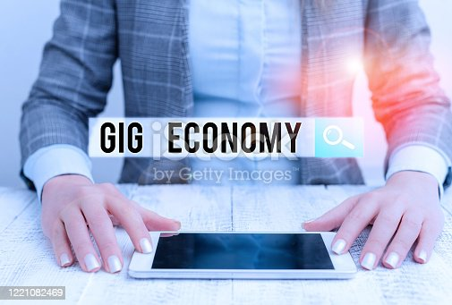 Handwriting text Gig Economy. Conceptual photo free market system in which temporary positions are common Business woman sitting with mobile phone on the table