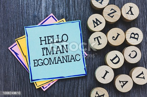 Handwriting text Hello I am An Egomaniac. Concept meaning Selfish Egocentric Narcissist Self-centered Ego Black wooden deck written sticky note beside some round woody alphabets