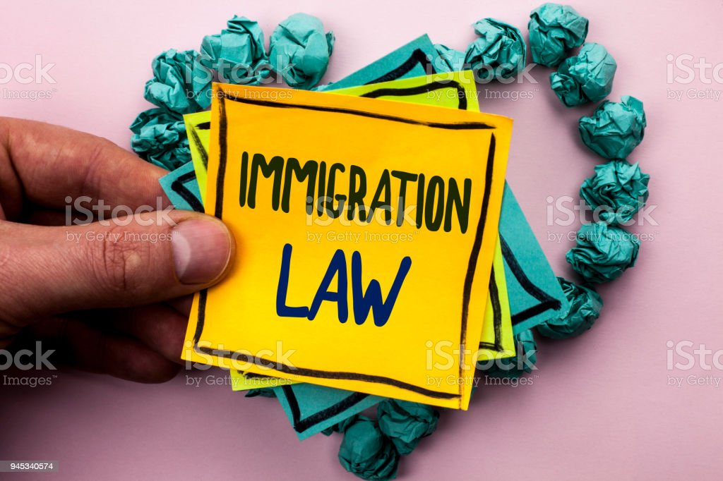 Handwriting text Immigration Law. Concept meaning National Regulations for immigrants Deportation rules written on Sticky Note Paper Holding by man plain background on Heart Paper Balls. stock photo