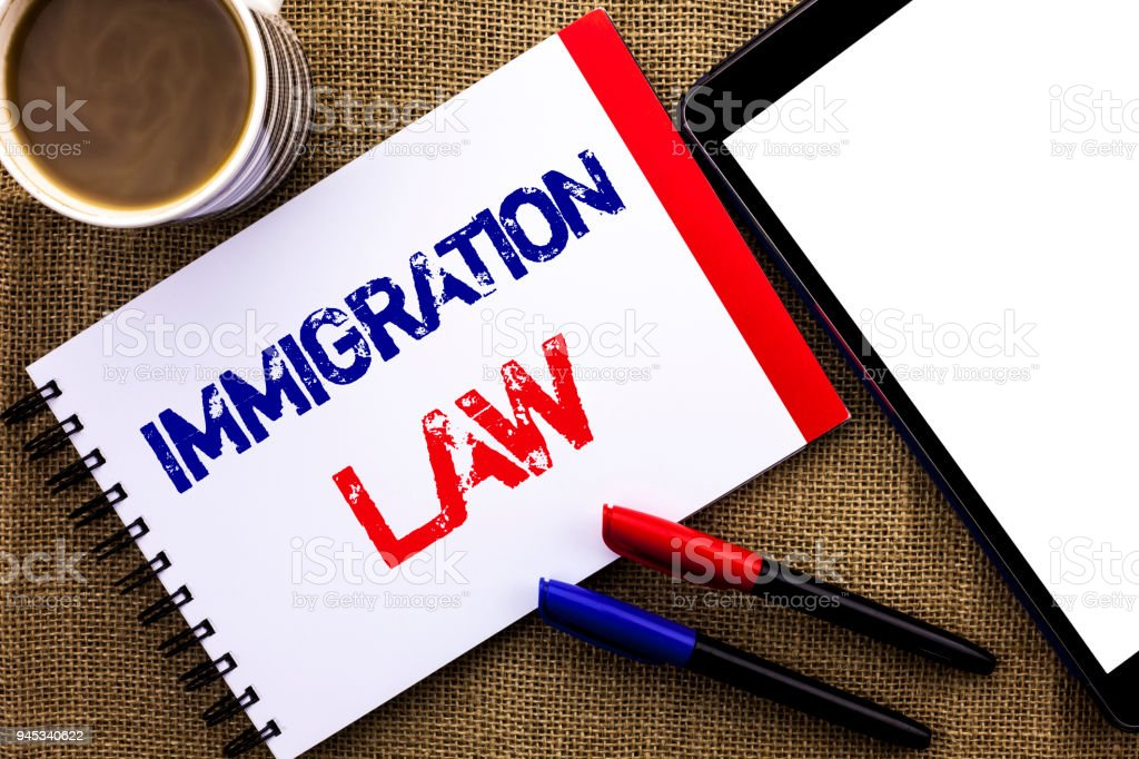 Handwriting text Immigration Law. Concept meaning National Regulations for immigrants Deportation rules written on Notebook Book on the jute background Tablet Coffee Cup and Pens next to it. stock photo