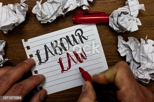 istock Handwriting text Labour Law. Concept meaning Rules implemented by the state between employers and employee Man holding marker notebook page crumpled papers several tries mistakes. 1071572054