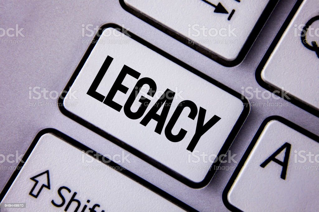 Handwriting text Legacy. Concept meaning Transmitted Received from an ancestor Money Properties given by will written on the White Keyboard Key with copy space. Top view. stock photo