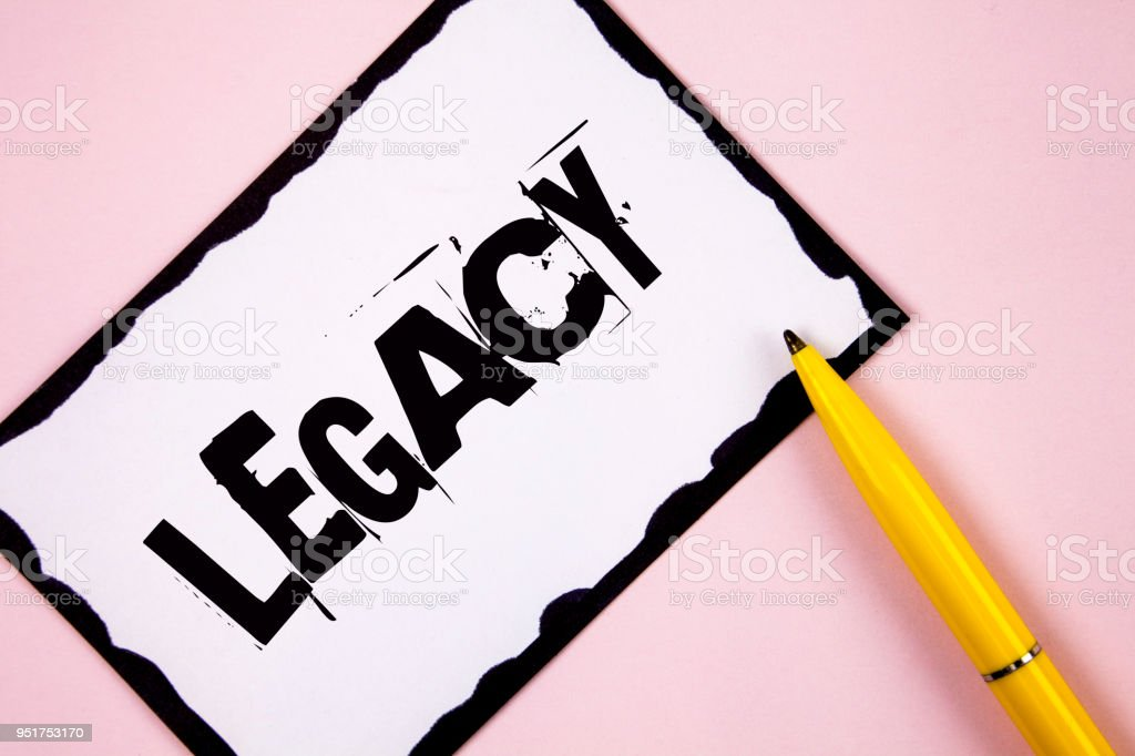 Handwriting text Legacy. Concept meaning Transmitted Received from an ancestor Money Properties given by will written on White Sticky note paper on plain Pink background Pen next to it. stock photo