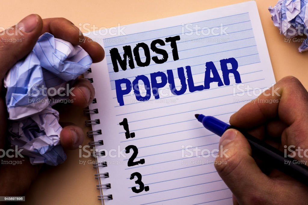 Handwriting text Most Popular. Concept meaning Top Rating Bestseller Favorite Product or Artist 1st in ranking written by Man on Notebook Book Holding Marker on the plain background. stock photo
