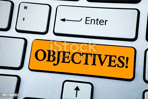 istock Handwriting text Objectives Motivational Call. Concept meaning Goals planned to be achieved Desired targets written on Orange Key Button on White Keyboard with copy space. Top view. 951766964