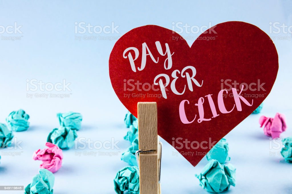 Handwriting text Pay Per Click. Concept meaning Get money from visitors Ads Advertising SEO Marketing written on Red Paper Heart holding by Clip on plain background Paper Balls next to it. – zdjęcie