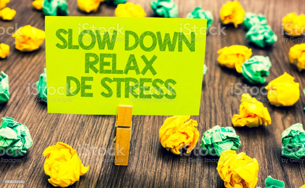 Handwriting text Slow Down Relax De Stress. Concept meaning Have a break reduce stress levels rest calm Paperclip retain written words yellow paper paper lobs laid on wooden floor. stock photo