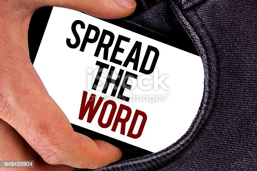 istock Handwriting text Spread The Word. Concept meaning Run advertisements to increase store sales many fold written on Mobile Screen holding in the Hand on Jeans background. 949453904