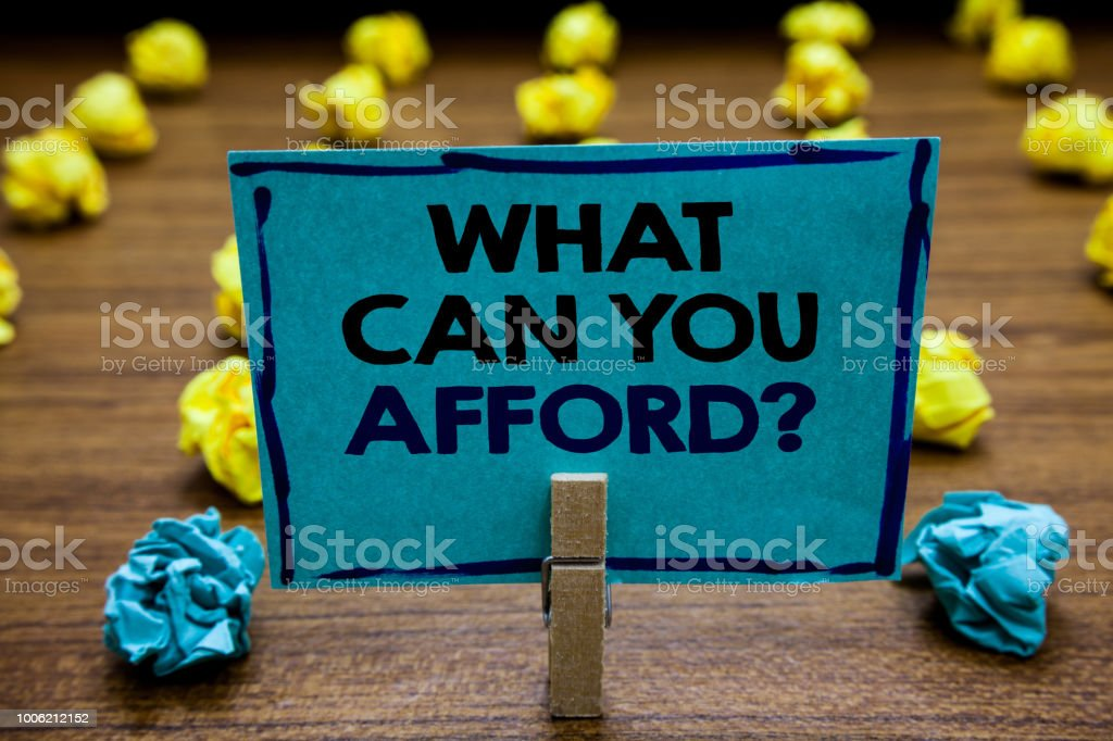 Handwriting text What Can You Afford question. Concept meaning Give us your budget availability of money Blurry wooden deck yellow and blue lob on ground paper clip grip page with text. stock photo